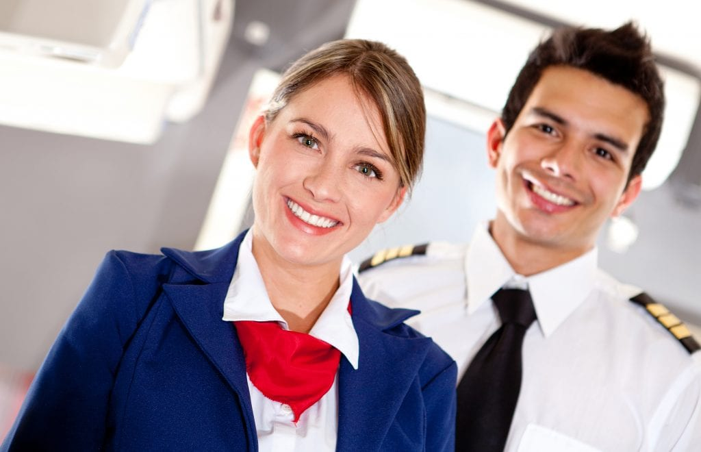 Male and female flight attendants on plane