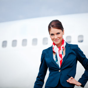 Outdoor portrait of a beautiful flight attendant standing in front of an aircraft and smiling at the camera.
